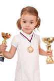 Girl with a gold medal and cups. Stock Photos