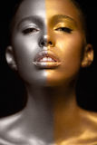 Girl with gold and silver skin in the image of an Oscar. Art image beauty face. Picture taken in the studio on a black background royalty free stock images