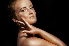 Girl with golden bodyart on a black Stock Photography