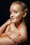 Girl with golden bodyart on a black Royalty Free Stock Photo
