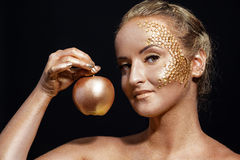 Girl with golden bodyart posing with golden apple Stock Photography