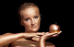Girl with golden bodyart posing with golden apple Stock Photos