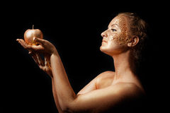 Girl with golden bodyart posing with golden apple Royalty Free Stock Images