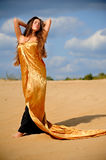Girl in golden cloack. Girl in golden cloak on the sand Royalty Free Stock Photos