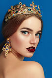 Girl with a golden crown and golden earrings. The crown with precious stones, diamond, sapphire. Earrings in the shape of a cross Stock Photo