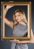 Girl with golden frame Stock Photography