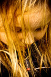 Girl with golden hair. Closeup portrait of little girl with face partially hidden by her long hair in golden evening sunlight Stock Photo
