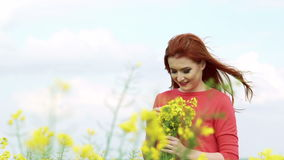 Girl with golden hair with bouquet of bloom smiling in the field. Slowly. Pretty girl with golden hair with bouquet of bloom smiling in the field. Slowly stock video footage