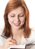 Girl with golden hair makes notes on a pad Stock Photo