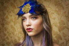 Girl with golden makeup and blue head accessorie Royalty Free Stock Photo