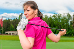 Girl with a golf a club turned Royalty Free Stock Photography