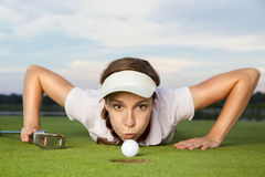 Girl golf player blowing ball into cup. Desperate young woman golf player with putter in hand lying on green and blowing golf ball into cup, close up Stock Image