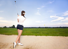 Girl golf player in bunker chipping ball. Woman golfer chipping golf ball out of sand trap onto green Royalty Free Stock Image