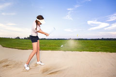 Girl golf player chipping ball in bunker. Young woman golfer chipping golf ball out of sand trap onto green with sand wedge and sand caught in motion Stock Photo