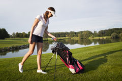 Girl golf player with golf bag. Royalty Free Stock Photo