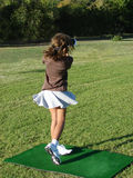 Girl Golfer. Young female golfer during a shot at a lesson, standing on a range mat Royalty Free Stock Photography