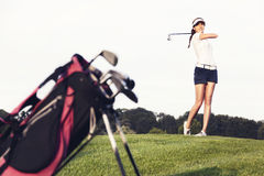 Girl golfer hitting the ball on golf course. royalty free stock photos