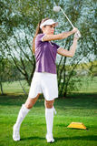 Girl golfer hitting the ball. Girl golf player hitting ball on golf course Royalty Free Stock Images