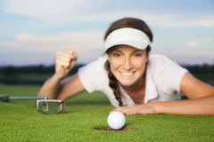 Girl golfer looking at ball dropping into cup. Happy woman golf player lying on green after successful shot. Focus on ball dropping into hole Stock Photos