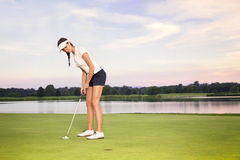 Girl golfer putting. Smiling woman golf player putting on green with lake in background Stock Photography