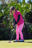 Girl golfer is putting. Girl golfer on the putting green aims a ball Royalty Free Stock Photography