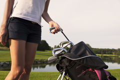 Girl golfer taking out iron from golf bag. Woman golf player taking out golf club from golf bag on golf course, close up royalty free stock photos