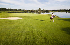 Girl golfer walking on golf course with golf bag. Female golf player walking towards green on fairway carrying golf bag with clubs, lake in background stock photo