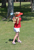 Girl Golfing. Little girl swinging golf club Royalty Free Stock Images