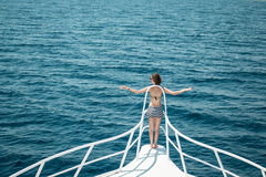 Girl with good body stay on rostrum in open sea Royalty Free Stock Image