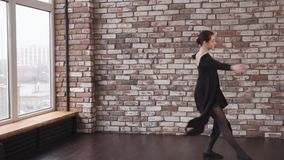 Young brunette dancer is performing jumps and rotating in a dance class. Girl is in good physical shape is doing leaps in dance. She is training for dancing stock video footage
