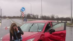 Girl got into car accident on the road in the heavy rain, she talks on the phone. Portrait of an emotional girl in the rain near a broken car on the road, she stock video