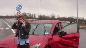 Girl got into car accident on the road in the heavy rain, she talks on the phone. A young girl got into a car accident on the road in the rain, she holds her stock video footage