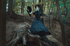 Girl in gothic dress standing among the snags forest. Girl in gothic dress standing among the snags in the forest. In hands holds a fan royalty free stock images