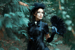 Girl in the Gothic image of walks park. Girl in the Gothic image of walks in the park. In her hands she holds a fan royalty free stock photo