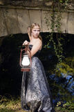 Girl. Gothic girl standing with a lantern in his hand at the bridge Stock Photo