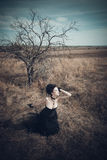 The girl in a Gothic suit. Young goth woman walking on field against a tree. Dark Queen in park. Fantasy black dress Royalty Free Stock Photo