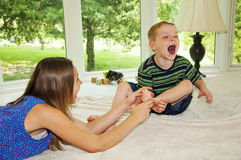 Girl grabbing foot, Boy being tickled laughing Royalty Free Stock Photo