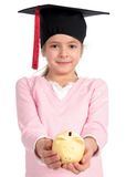Girl in graduation cap. Holding piggy bank Royalty Free Stock Image