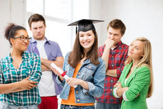 Girl in graduation cap with certificate Stock Images