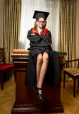 Girl in graduation cap and gown sitting on table at classic inte Stock Image
