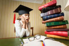 Girl in graduation cap looking at high heap of books on table at Royalty Free Stock Image