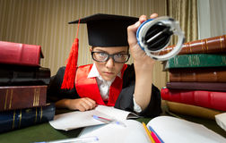 Girl in graduation cap putting stamp on document Stock Image