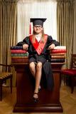 Girl in graduation cap sitting on desk between piles of books Stock Photos