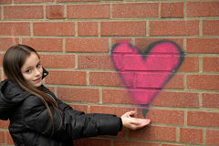 Girl and graffiti heart Stock Photos
