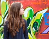 Girl by a graffiti wall. Girl looking for something in front of a graffiti wall Royalty Free Stock Photos