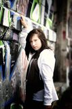 Girl on graffiti wall. A young woman standing next to a graffiti wall Royalty Free Stock Photo