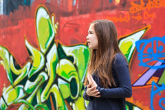 Girl by a grafitti wall. Girl looking for something in front of a graffiti wall royalty free stock photo