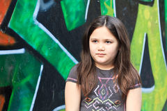 Girl by a grafitti wall. Girl standing in front of a graffiti wall stock photo