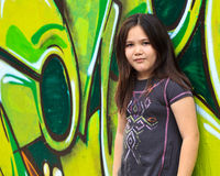 Girl by a grafitti wall. Girl standing in front of a graffiti wall royalty free stock photo