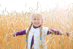 Girl in grainfield arms wide open smiling Stock Photography